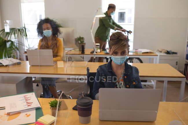 Grupo multi étnico de criativos masculinos e femininos que trabalham em mesas de escritório com telas de proteção, usando computadores portáteis. Saúde e higiene no local de trabalho durante a pandemia de Coronavirus Covid 19. — Fotografia de Stock