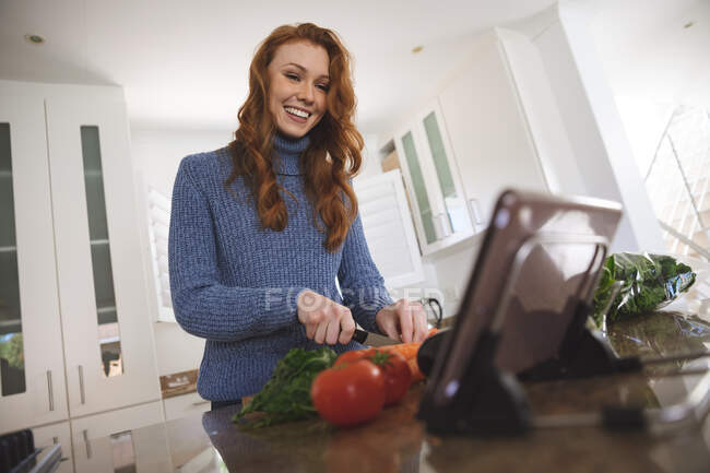 Caucasian woman spending time at home, chopping vegetables in the kitchen, using her digital tablet, smiling. Social distancing during Covid 19 Coronavirus quarantine lockdown. — Stock Photo