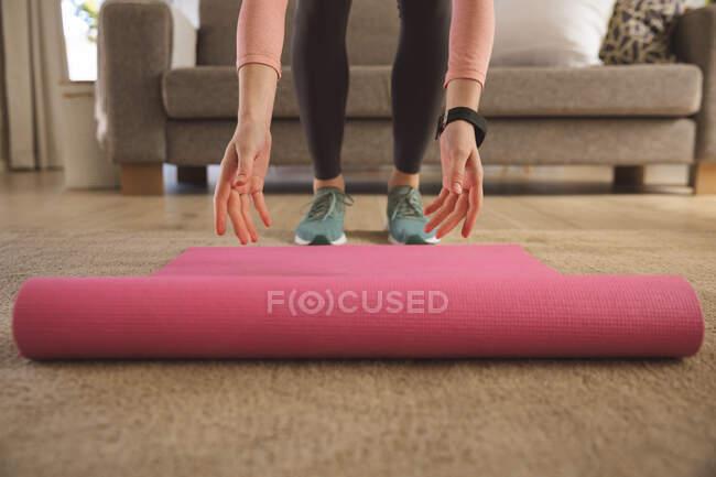 Женщина проводит время дома, в гостиной, разворачивает коврик для йоги, готовится к тренировкам. Социальное дистанцирование во время изоляции коронавируса Covid 19. — стоковое фото