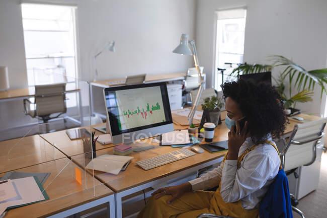 Donna di razza mista seduta alla scrivania in un ufficio moderno con una maschera facciale, che parla su smartphone e usa il computer. Salute e igiene sul luogo di lavoro durante la pandemia di Coronavirus Covid 19. — Foto stock