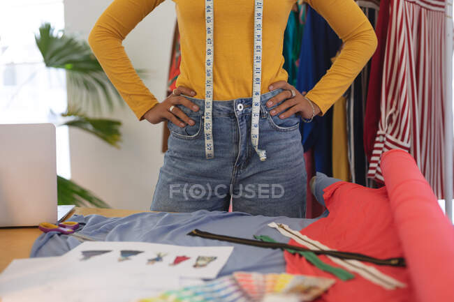 Средняя секция женского модельера в студии носит рулетку на шее. Здоровье и гиперактивность на рабочем месте во время коронавируса Ковид 19 пандемии. — стоковое фото