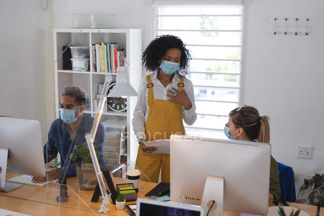 Mixed race and Caucasian female creative business colleague talking in office wearing face masks, male colleague in background. Health and hygiene in workplace during Coronavirus Covid 19 pandemic. — Stock Photo