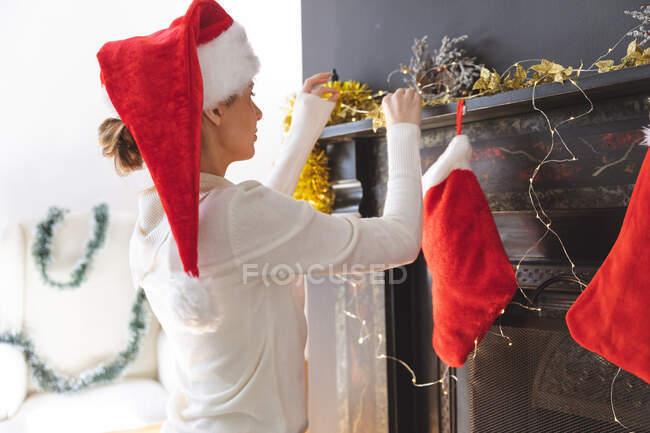 Donna caucasica trascorrere del tempo a casa a Natale, indossando il cappello di Babbo Natale, seduto sul pavimento in soggiorno, decorazione camino. Distanza sociale durante il blocco di quarantena Covid 19 Coronavirus. — Foto stock