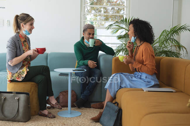 Multi ethnic group of male and female business creatives wearing face masks and distancing holding coffees and talking. Health and hygiene in workplace during Coronavirus Covid 19 pandemic. — Stock Photo