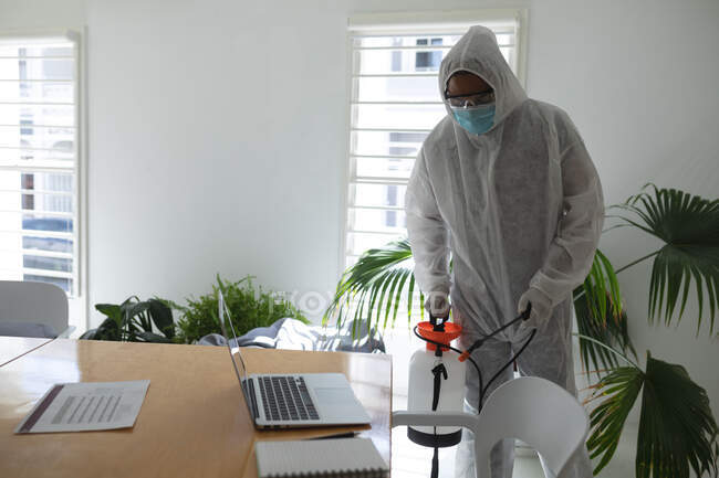 Mixed race male cleaner wearing anti-contamination overalls spraying disinfecting an office. Health and hygiene in the workplace during Coronavirus Covid 19 pandemic. — Stock Photo