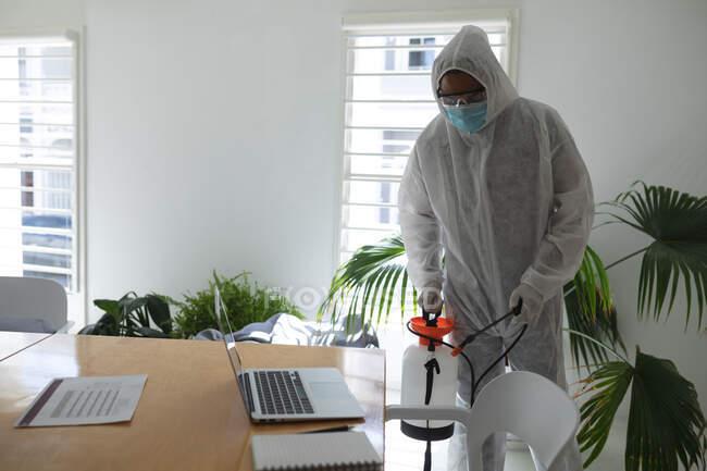 Pulitore maschio misto razza che indossa tuta anti-contaminazione spruzzando disinfezione un ufficio. Salute e igiene sul luogo di lavoro durante la pandemia di Coronavirus Covid 19. — Foto stock