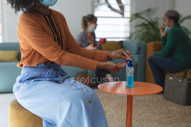 Mixed race female creative sitting on sofa in an office wearing face mask disinfecting hands with hand sanitizer. Health and hygiene in workplace during Coronavirus Covid 19 pandemic. — Stock Photo