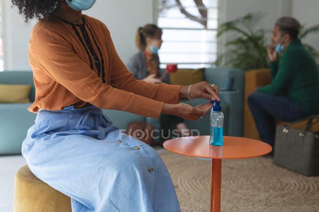 Misto razza femminile creativo seduto sul divano in un ufficio indossando maschera viso disinfettante mani con disinfettante per le mani. Salute e igiene sul luogo di lavoro durante la pandemia di Coronavirus Covid 19. — Foto stock
