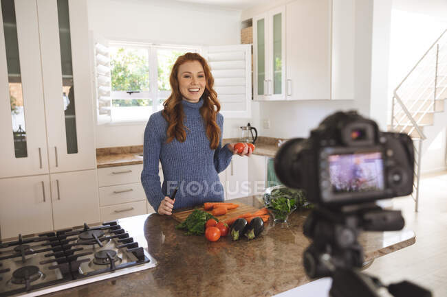 Caucasian woman spending time at home, chopping vegetables in the kitchen, recording it with a camera. Social distancing during Covid 19 Coronavirus quarantine lockdown. — Stock Photo