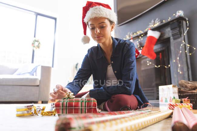 Donna caucasica trascorrere del tempo a casa a Natale, indossando il cappello di Babbo Natale, seduto sul pavimento in soggiorno, avvolgendo presente in carta. Distanza sociale durante il blocco di quarantena Covid 19 Coronavirus. — Foto stock