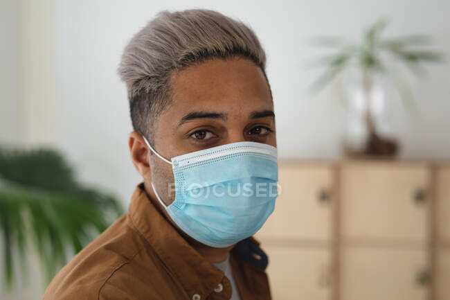 Portrait of mixed race male business creative standing in an office wearing face mask. Health and hygiene in workplace during Coronavirus Covid 19 pandemic. — Stock Photo