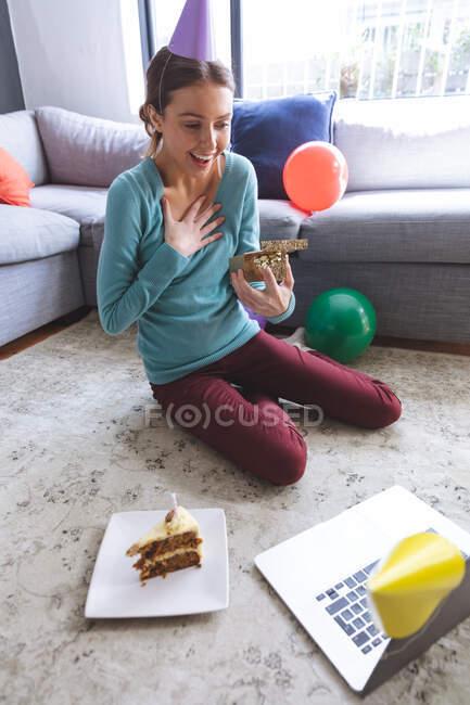 Mujer caucásica feliz pasar tiempo en casa, en sombrero de fiesta, sentado en el suelo utilizando la computadora durante el chat de vídeo, sosteniendo presente. Distanciamiento social durante el bloqueo de cuarentena del Coronavirus Covid 19. - foto de stock