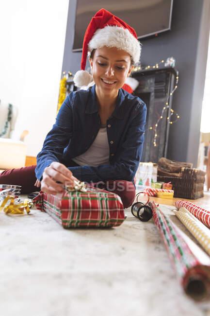 Donna in cappello Babbo Natale regalo avvolgente vicino al camino in soggiorno. Natale, stare a casa, distanza sociale. — Foto stock