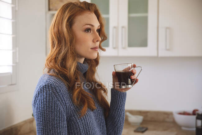 Caucasian woman spending time at home, in kitchen, looking serious, holding a cup, drinking coffee. Social distancing during Covid 19 Coronavirus quarantine lockdown. — Stock Photo