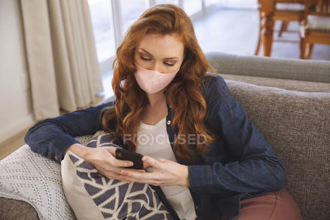 Caucasian woman spending time at home, in living room, using smartphone, wearing a face mask. Social distancing during Covid 19 Coronavirus quarantine lockdown. — Stock Photo