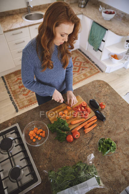 Caucasian woman spending time at home, chopping vegetables in the kitchen, focusing. Social distancing during Covid 19 Coronavirus quarantine lockdown. — Stock Photo