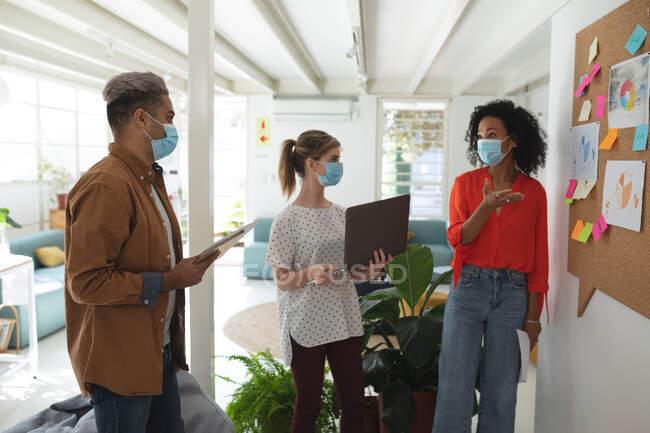 Multi gruppo etnico di uomini e donne creativi d'affari in piedi brainstorming in ufficio moderno indossando maschere facciali. Salute e igiene sul luogo di lavoro durante la pandemia di Coronavirus Covid 19. — Foto stock