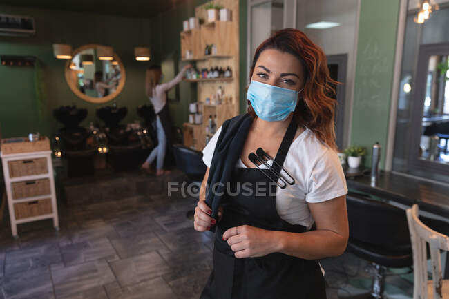 Portrait of a Caucasian female hairdresser working in hair salon wearing face mask, posing for a photo. Health and hygiene in workplace during Coronavirus Covid 19 pandemic. — Stock Photo