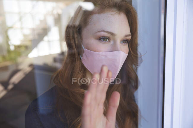 An attractive, ginger Caucasian woman spending time at home, in living room, looking out of the window, wearing a face mask. Social distancing during Covid 19 Coronavirus quarantine lockdown. — Stock Photo