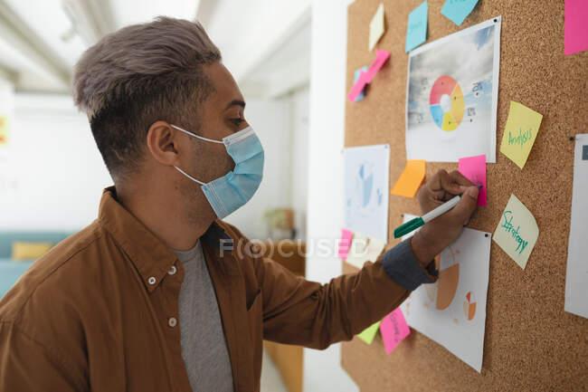 Misto razza maschile business creativo in piedi in un ufficio con indosso maschera viso scrittura note su una bacheca. Salute e igiene sul luogo di lavoro durante la pandemia di Coronavirus Covid 19. — Foto stock