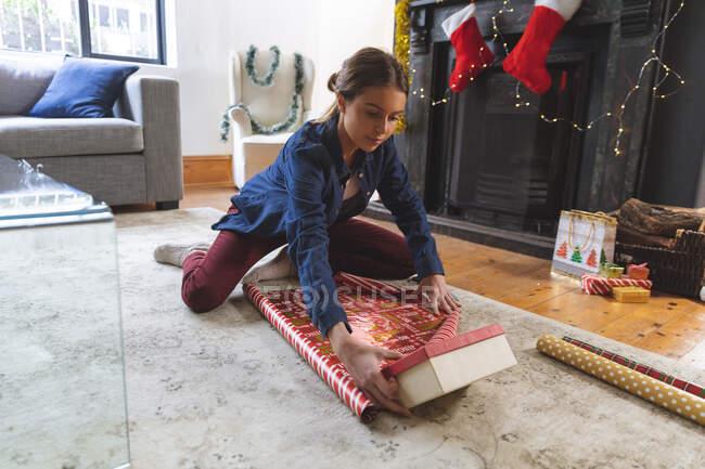 Donna caucasica trascorrere del tempo a casa a Natale, seduto sul pavimento vicino al camino in soggiorno, avvolgendo regali. Distanza sociale durante il blocco di quarantena Covid 19 Coronavirus. — Foto stock