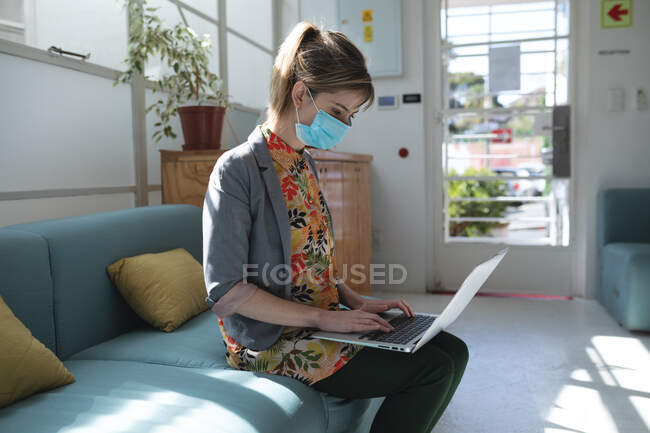 Caucasian female business creative sitting on sofa in an office wearing face mask using her laptop. Health and hygiene in workplace during Coronavirus Covid 19 pandemic. — Stock Photo