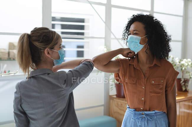 Razza mista e colleghe caucasiche indossano maschere facciali in carica, distanziando e salutando toccando i gomiti. Salute e igiene sul luogo di lavoro durante la pandemia di Coronavirus Covid 19. — Foto stock