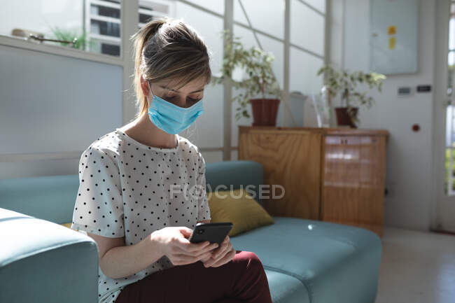 Caucasian female business creative sitting on sofa in an office wearing face mask using her smartphone. Health and hygiene in workplace during Coronavirus Covid 19 pandemic. — Stock Photo