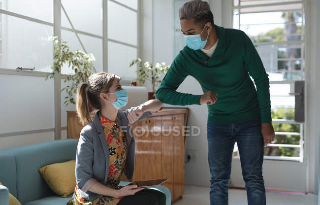 Mixed race male and Caucasian female colleagues wearing face masks in office, distancing and greeting by touching elbows. Health and hygiene in workplace during Coronavirus Covid 19 pandemic. — Stock Photo