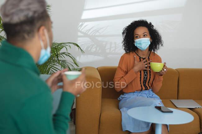 Creativi aziendali misti di razza maschile e femminile che indossano maschere facciali e prendono le distanze tenendo caffè e parlando in sala riunioni. Salute e igiene sul luogo di lavoro durante la pandemia di Coronavirus Covid 19. — Foto stock