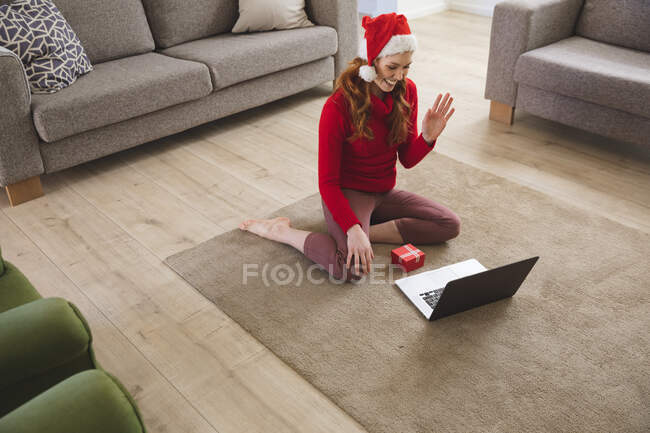 Caucasian woman spending time at home, in living room, smiling, wearing Christmas hat, waving during a video call. Social distancing during Covid 19 Coronavirus quarantine lockdown. — Stock Photo