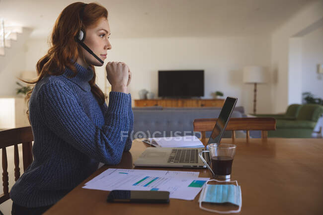 Caucasian woman spending time at home, in the kitchen, working from home, using her laptop,  wearing a headset. Social distancing during Covid 19 Coronavirus quarantine lockdown. — Stock Photo