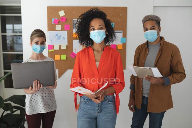 Ritratto di gruppo multietnico di colleghi d'affari creativi uomini e donne che indossano maschere facciali in un ufficio. Salute e igiene sul luogo di lavoro durante la pandemia di Coronavirus Covid 19. — Foto stock