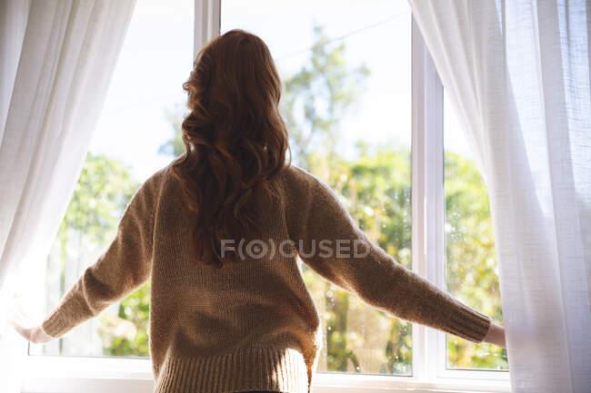 Vue arrière d'une femme caucasienne rousse passant du temps à la maison, dans le salon, regardant par la fenêtre. Distance sociale pendant le confinement en quarantaine du coronavirus Covid 19. — Photo de stock