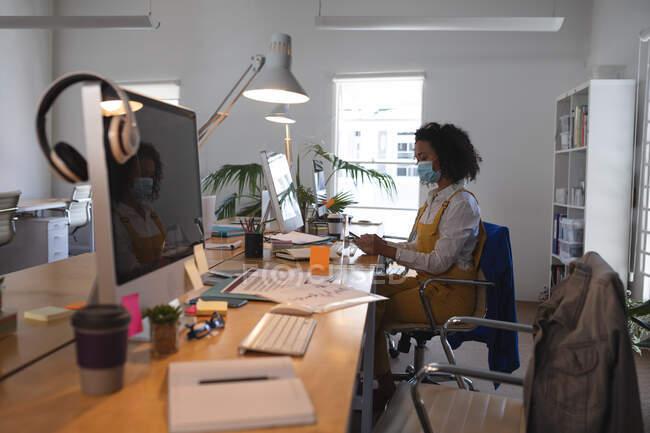 Donna mista che lavora alla scrivania in un ufficio moderno indossando una maschera facciale e utilizzando lo smartphone. Salute e igiene sul luogo di lavoro durante la pandemia di Coronavirus Covid 19. — Foto stock