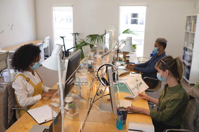 Grupo multi étnico de criativos masculinos e femininos que trabalham em mesas de escritório com telas de proteção, usando computadores. Saúde e higiene no local de trabalho durante a pandemia de Coronavirus Covid 19. — Fotografia de Stock