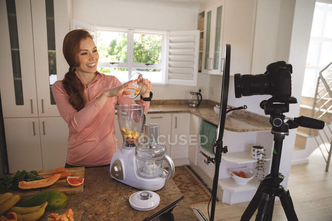 Caucasian woman spending time at home, putting fruit in a blender, recording it with a camera. Social distancing during Covid 19 Coronavirus quarantine lockdown. — Stock Photo