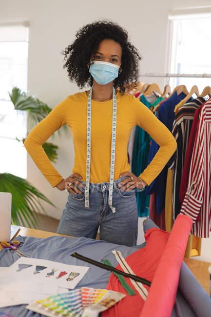 Портрет женщины-модельера смешанной расы в студии в маске для лица и рулетке на шее, смотрящей в камеру. Здоровье и гиперактивность на рабочем месте во время коронавируса Ковид 19 пандемии. — стоковое фото
