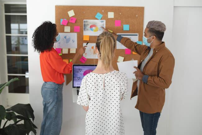 El grupo multiétnico de creativos de negocios masculinos y femeninos se mantiene en pie durante la lluvia de ideas en la oficina moderna con máscaras faciales. Salud e higiene en el lugar de trabajo durante la pandemia de Coronavirus Covid 19. - foto de stock