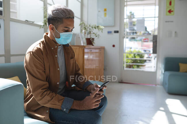 Mixed race male business creative sitting on sofa in an office wearing face mask using his smartphone. Health and hygiene in workplace during Coronavirus Covid 19 pandemic. — Stock Photo