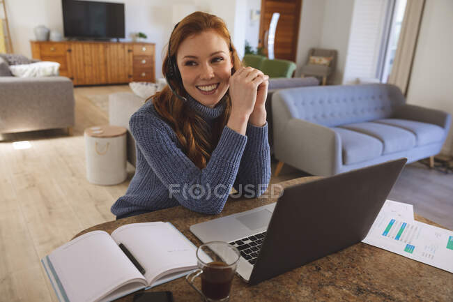 Caucasian woman spending time at home, in the kitchen, working from home, using her laptop,  wearing a headset, smiling. Social distancing during Covid 19 Coronavirus quarantine lockdown. — Stock Photo