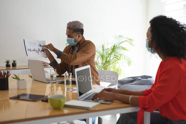 Mixed race male and female business creatives in meeting wearing face masks discussing documents. Health and hygiene in the workplace during Coronavirus Covid 19 pandemic. — Stock Photo