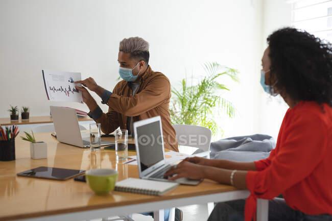 Creativi aziendali misti di razza maschile e femminile nell'incontro indossando maschere facciali che discutono documenti. Salute e igiene sul luogo di lavoro durante la pandemia di Coronavirus Covid 19. — Foto stock