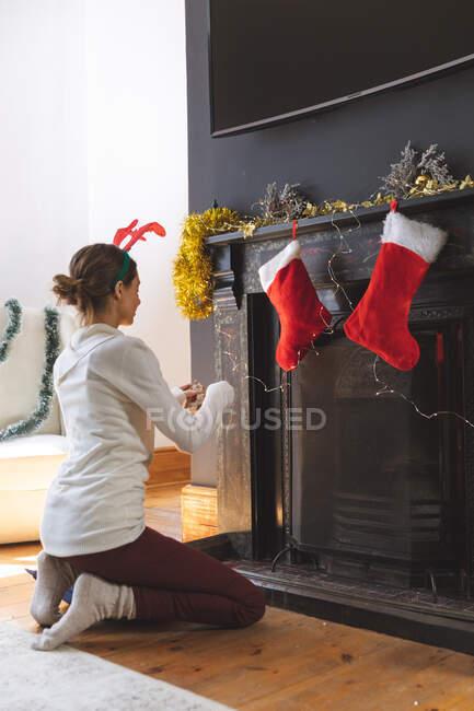 Donna caucasica trascorrere del tempo a casa a Natale, indossando corna di renna, seduto sul pavimento in soggiorno, decorazione camino. Distanza sociale durante il blocco di quarantena Covid 19 Coronavirus. — Foto stock