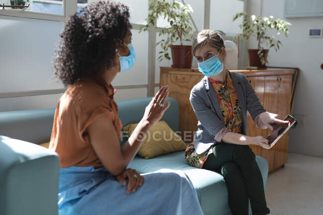 Mixed race and Caucasian female business creatives wearing face masks and distancing on sofa, talking and using tablet in office. Health and hygiene in workplace during Coronavirus Covid 19 pandemic. — Stock Photo