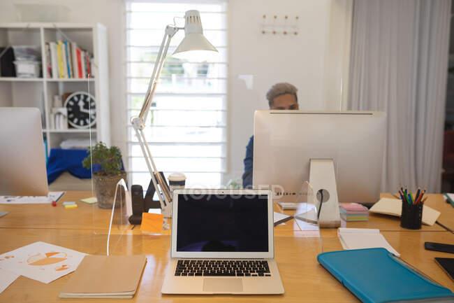La raza mixta masculino creativo sentado en el escritorio en una oficina moderna, utilizando un ordenador, ordenador portátil en un primer plano. Salud e higiene en el lugar de trabajo durante la pandemia de Coronavirus Covid 19. - foto de stock