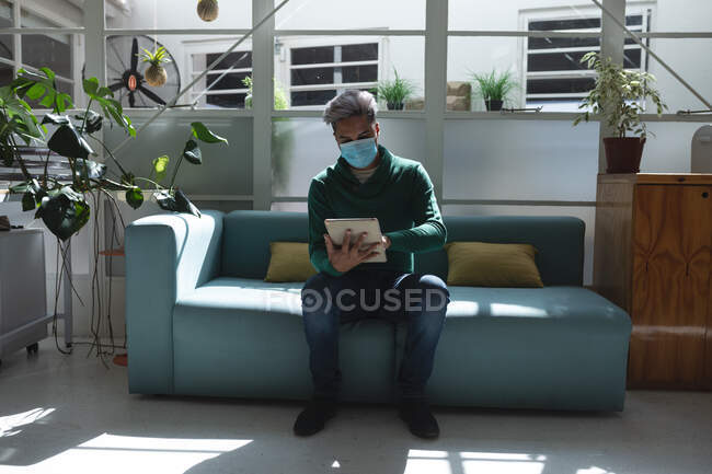 Mixed race male business creative sitting on sofa in an office wearing face mask using his tablet. Health and hygiene in workplace during Coronavirus Covid 19 pandemic. — Stock Photo