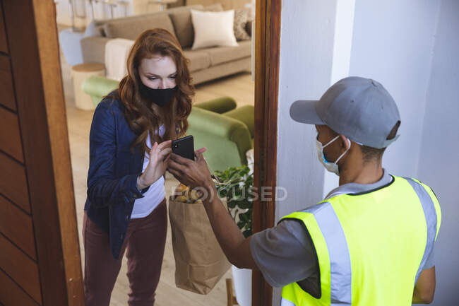 Caucasian woman spending time at home, taking order from delivery man. Social distancing during Covid 19 Coronavirus quarantine lockdown. — Stock Photo