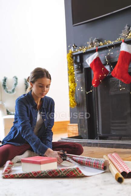 Donna caucasica trascorrere del tempo a casa a Natale, seduto sul pavimento vicino al camino in soggiorno, tagliando carta da imballaggio. Distanza sociale durante il blocco di quarantena Covid 19 Coronavirus. — Foto stock