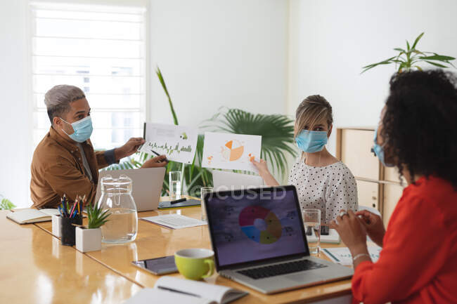 Multi ethnic group of male and female business creatives in meeting wearing face masks discussing documents. Health and hygiene in the workplace during Coronavirus Covid 19 pandemic. — Stock Photo